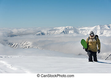 Manful snowboarder walking with the snowboard on the ...