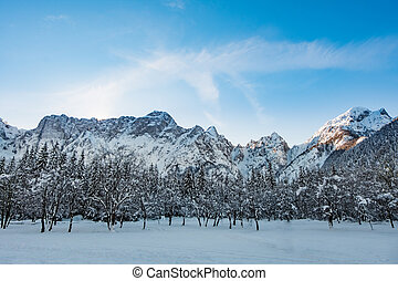 Mangart mountain range seen from snow covert frozen lake...