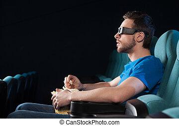 manger, film regardant, cinema., hommes, jeune, côté, cinéma, pop-corn, vue, excité, lunettes