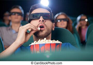manger, film regardant, cinema., hommes, jeune, cinéma, pop-corn, excité, lunettes