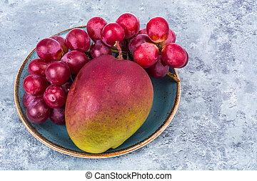 Mango and grapes on plate