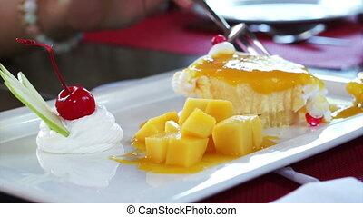 Eating Mango Cheese Cake on white plate with fresh fruit decoration