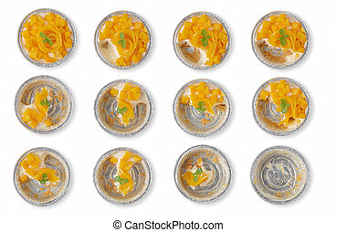 Mango cheesecake in aluminum foil cup isolated over white background.