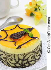 Mango chocolate cake decorated with mint leaves and swirls