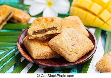 Mango cookies in wooden bowl with palm leaf.