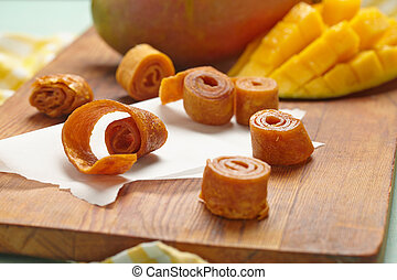 Mango fruit leather rolls on a cutting board