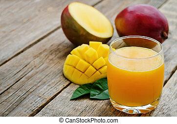 mango juice and fresh mango on a dark wood background....