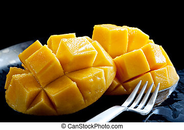 Mango - Luscious cut mango on a black plate with fork, ready...