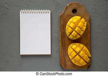 Mango on rustic wooden board, blank notepad over concrete...