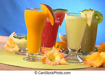 Mango, pineapple, watermelon and kiwi smoothies surrounded by gladiolus flower (Selective Focus, Focus on the mango and pineapple smoothies in the front)