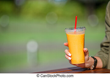 Mango smoothie in a glass in female hand close up