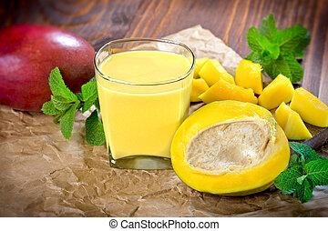 Mango smoothie (mango juice) and fresh mango on table