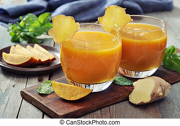 Mango smoothie in glass with ginger on wooden background