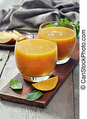 Mango smoothie in glass with mint on wooden background