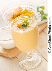 mango smoothie - fresh mango smoothie on wood background