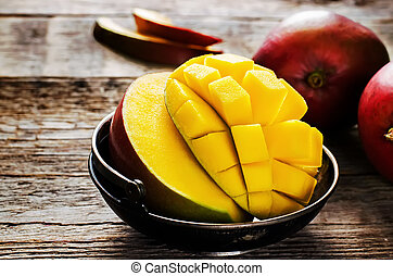 mango on a dark wood background. tinting. selective focus on...