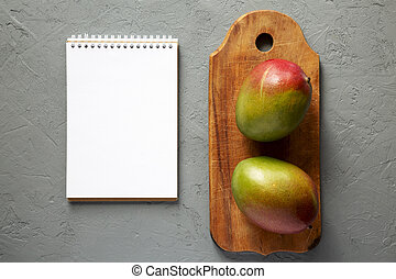 Mangoes on rustic wooden board, blank notepad over concrete...