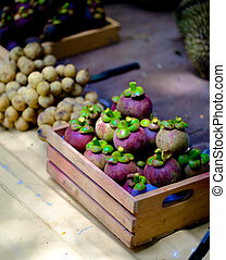Mangosteen is in a small wooden crate.