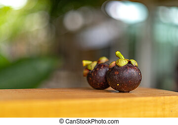 Mangosteen on the wooden plate, with blur bokeh green nature background.