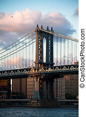 Manhattan bridge and river with cloudy sunset sky, New Yo
