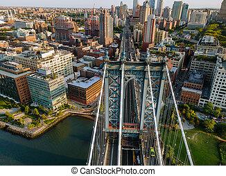 Manhattan Bridge with Brooklyn New York City skyscrapers city over Hudson River.