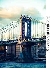 Manhattan bridge with cloudy sky before sunset in vintage style, New York