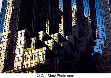 Manhattan building is reflected in the facade of a modern ...