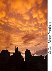 Manhattan buildings in silhouette with orange mammatus...