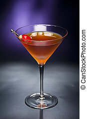 Manhattan cocktail garnished with a cherry and lemon with blue black back ground