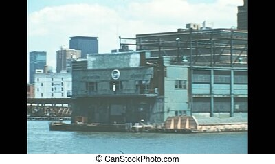 Archival of Manhattan skyline, sea view from Hudson river sightseeing cruise. Old famous skyscrapers and Starrett Lehigh warehouse and office building of New York city. United States America in 1976.