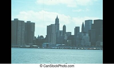 Archival of Manhattan skyline, sea view from Hudson river sightseeing cruise. Old Twin Towers skyscrapers and office buildings of New York city. United States America in 1976.