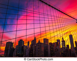 Manhattan skyline at sunset with the cables of the brooklyn bridge