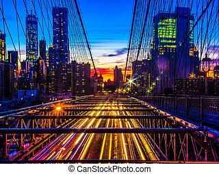 Manhattan skyline at sunset with the traffic on the brooklyn bridge