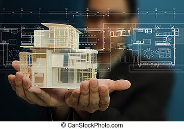 Manholding a model of a house in his hands.