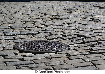 Manhole Cover on a cobblestone street in DUMBO, Brooklyn.