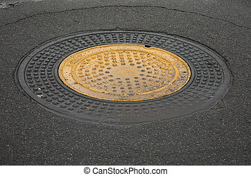 Manhole cover - Yellow manhole cover in black paved street.