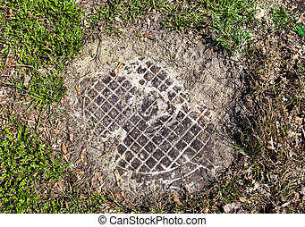 Manhole with metal cover sunk into the ground and grass