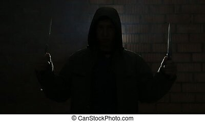 Maniac with knives waiting for his victim in the dark -...
