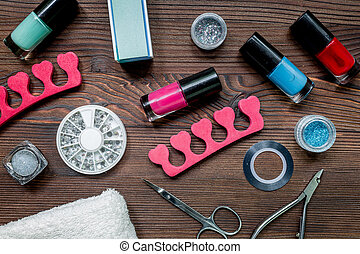 manicure and hands care set with nippers, cuticle scissors on wooden background top view