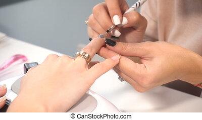 Manicure artist female making professional manicure in spa...