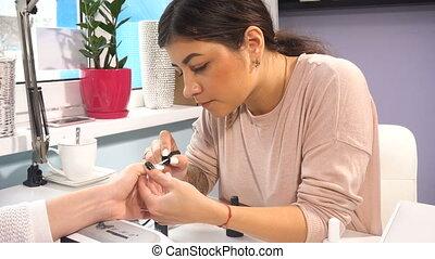 Manicure artist making professional manicure in spa salon