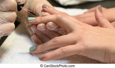 Manicure master applies cuticle oil for nails on left hand
