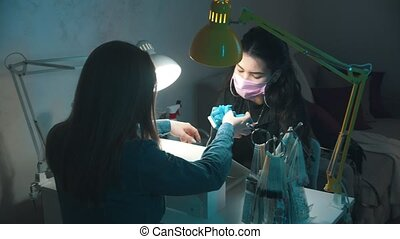 Manicure master in mask and gloves doing manicure - cleans the cuticle using device. Mid shot