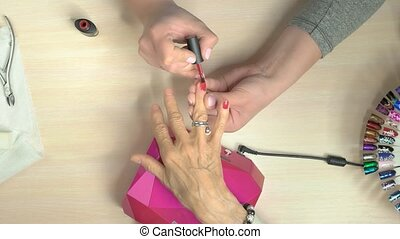 Manicure master professionally doing manicure. The process...