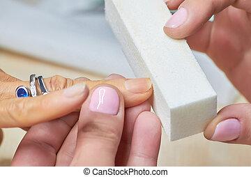 Manicure nail buffering close up.