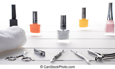 Manicure or pedicure set tools are placed on a table with a white towel in the beauty salon. Equipment for beauty shop or beauty parlour. Set for home manicure and nail care.