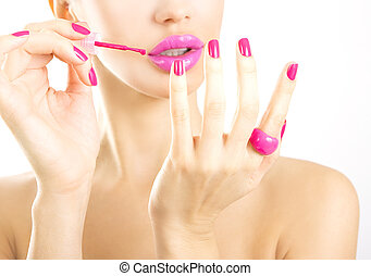 manicure process - beautiful girl makes pink manicure on a white background (bright makeup)