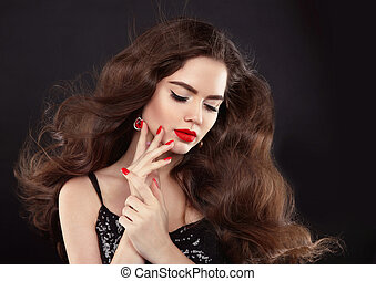 Manicure. Red lips makeup. Beautiful Brunette girl with long blowing shiny wavy hair. Fashion earring jewelry. Elegant model with manicured nails over black background.