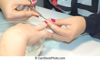 manicure specialist care by finger nail in beauty salon. Manicurist uses professional manicure tool.