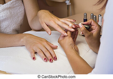 Manicure - A young woman getting her nails painted during a...
